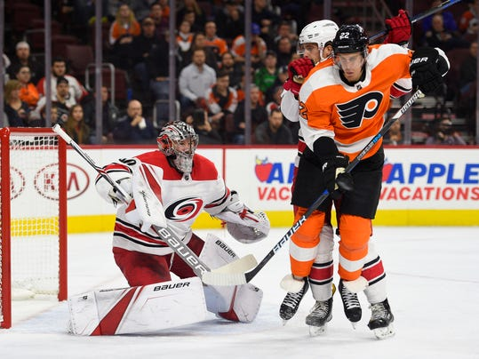 Carolina Hurricanes goalie Cam Ward, left, looks for the puck behind a screen by Philadelphia Flyers' Dale Weise (22) during the second period of an NHL hockey game, Thursday, March 1, 2018, in Philadelphia. (AP Photo/Derik Hamilton)