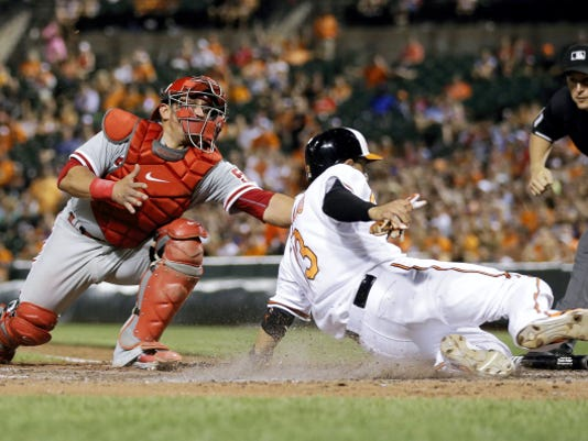 Baltimore Orioles' Manny Machado, right, slides past Philadelphia Phillies catcher Carlos Ruiz for a run on a double by Travis Snider in the fifth inning of Tuesday's game in Baltimore.