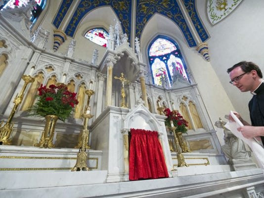 Father Sawicki, at the Church of the Immaculate Conception — St. Mary's in York, changes a tabernacle veil from red to white.