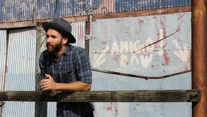 Joel Adam Russell, pictured, stands in front of the namesake graffiti which is located a few doors down from Amigo Row, 514 E. Main St., Visalia, which will be having a soft opening party/concert on Friday.