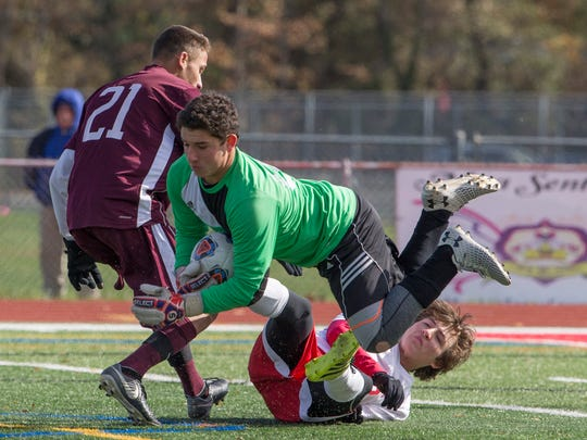 Ocean goalie Max Winters dives for ball and avoide a team mate while keeping Toms River South's Isaiah Dominguez from getting a shot on goal. Toms River South Boys Soccer edges out Ocean Twp 2-1in  Central Group III final in Ocean Township NJ on November 10, 2017.