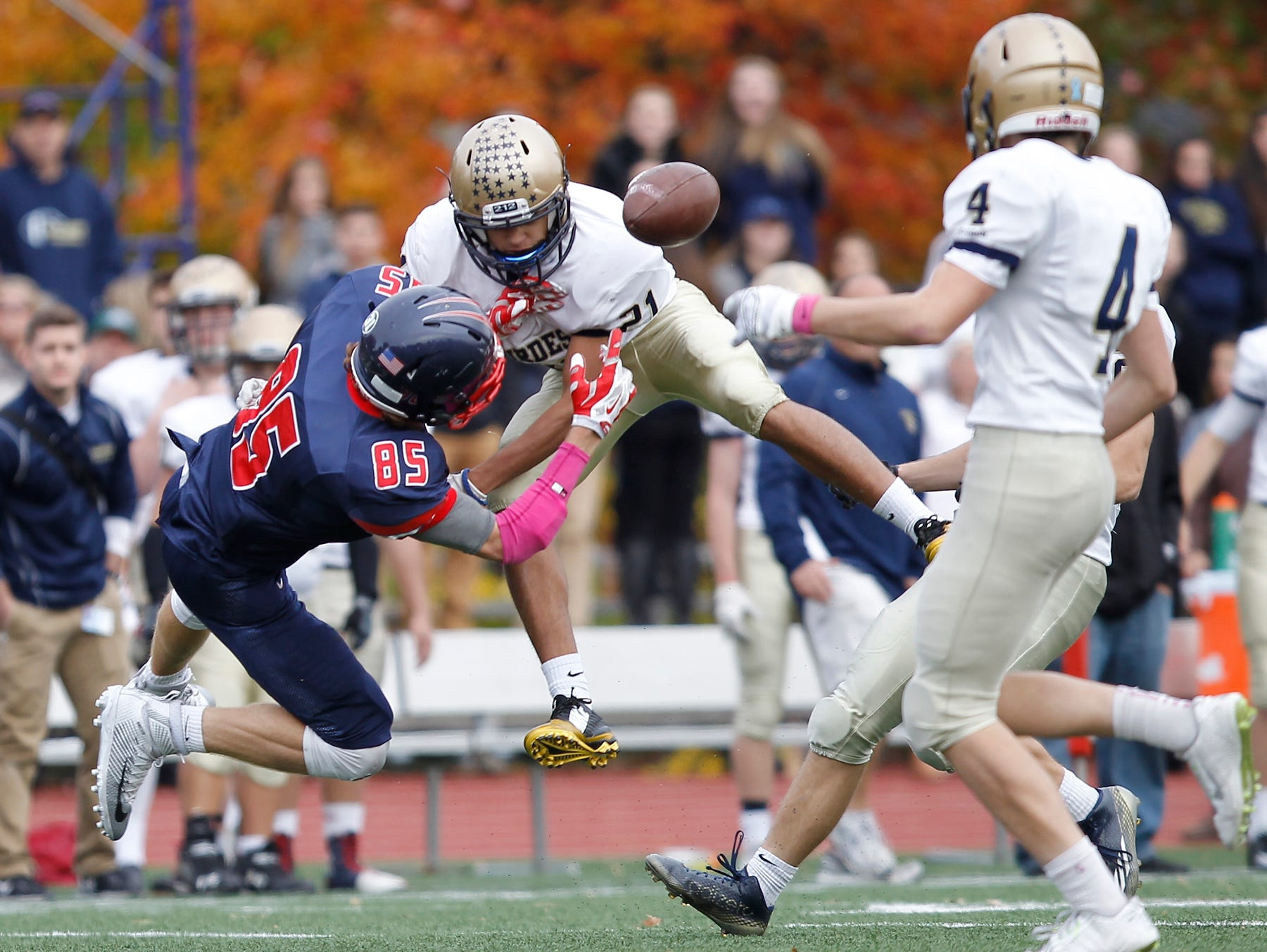 Eastchester's Andrew Schultz (85) looses possession of a pass after a hit by Lourdes' defensive back Nick Santacroce (21) during their 19-27 loss to Our Lady of Lourdes High School in the class A semi-final football game in Eastchester on Saturday, Oct. 31, 2015.