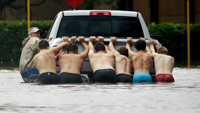 A group of people push a stalled pickup through a flooded street in Houston on Aug. 27, 2017, after Tropical Storm Harvey dumped heavy rains.
