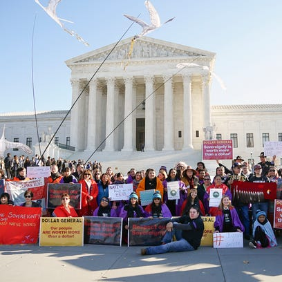 Protesters stand together in front of the U.S. Supreme