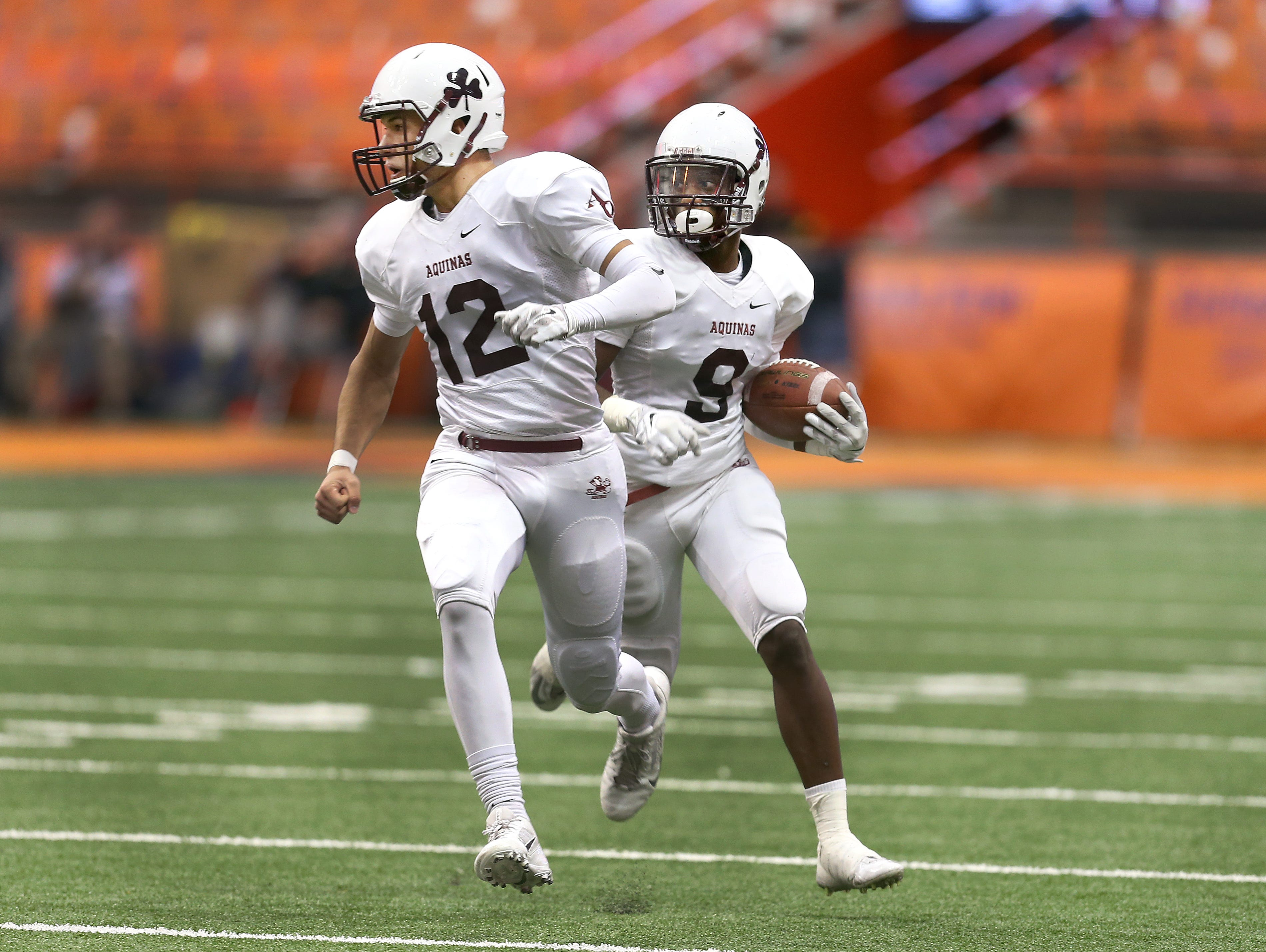 Aquinas quarterback Jake Zembiec (12) looks to block after receiver Earnest Edwards reversed direction after a catch. Aquinas beat Saratoga Springs 44-19 to win the State Class AA title.