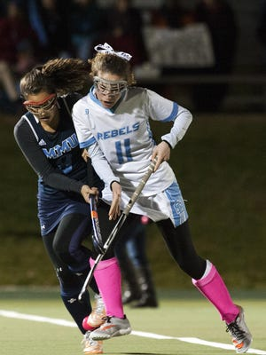 South Burlington's Willow Yager (11) and MMU's Margaret Thompson (9) battle for the ball during the semifinal field hockey game between the Mount Mansfield Cougars and the South Burlington Rebels at Middlebury College on Monday night in Middlebury.