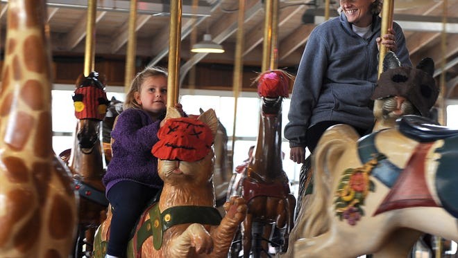 Mckenzie Logue, 4, and Melissa Lewis take a spin on the mask-wearing carousel animals.