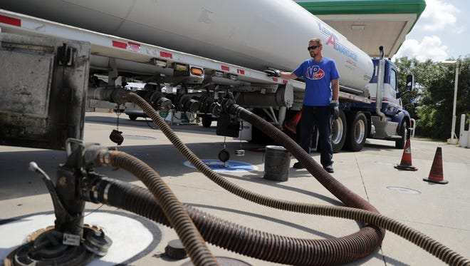 Josh Burns, a driver with Kenan Advantage Group Inc., waits near his tanker while gasoline is unloaded at the BP Neenah Standard Service Station on Main Street in Neenah.