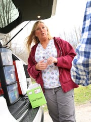Public health nurse Jackie McClintock, operating a mobile needle-exchange program, talks March 24, 2016, with an IV drug user in Austin, Ind.