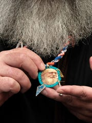 Kevin Coupe of Kansas City, Mo., shows a badge he made with symbols from Father Solanus Casey's life before the late priest's beatification Mass on Nov. 18, 2017, in Detroit.
