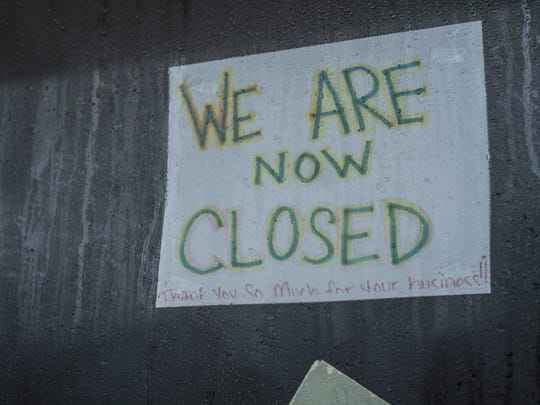 A sign hangs in the window of the former, now-vacant