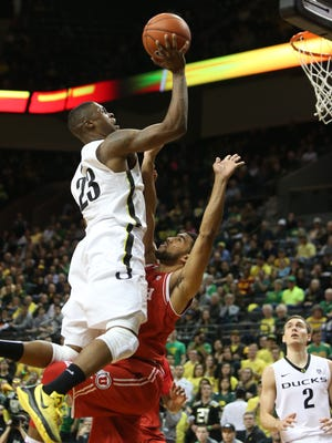 Oregon's Elgin Cook, left, drives over Utah's Isaiah Wright for a layup and a foul call during the first half of an NCAA college basketball game Sunday, Feb. 7, 2016, in Eugene, Ore.