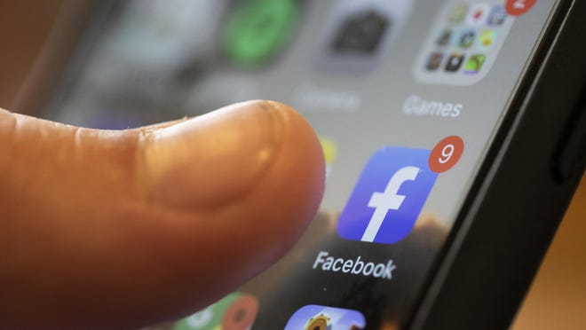 In this Sunday, Aug. 11, 2019, photo an iPhone displays the Facebook app in New Orleans.