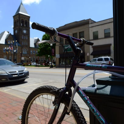 A bicycle rests locked to a lamp post Monday on Main