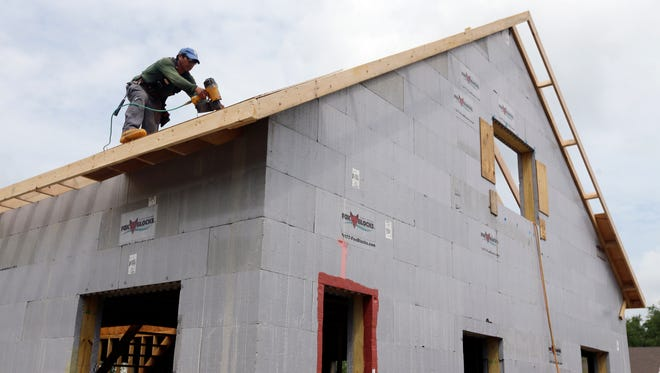 A  construction worker drills on the  roof of a new home  in New Paltz, N.Y.