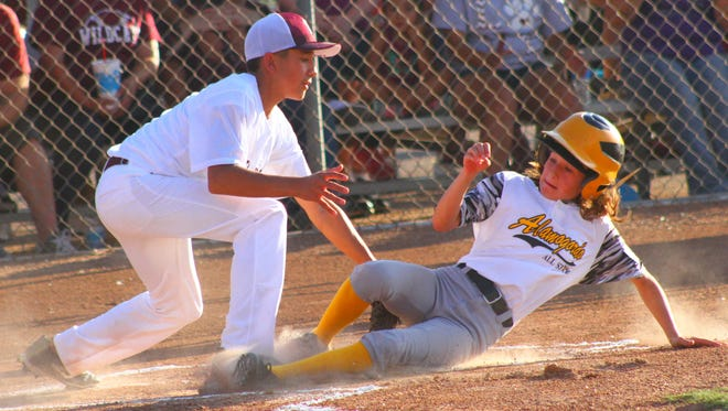 Rotary Little League's Caitlyn Bowman slides safely into home plate Sunday night at the Griggs Sports Complex.