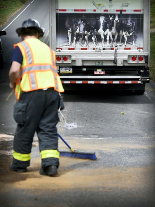 CRASH IN NORTH LEBANON TOWNSHIP: Avon Citizens firefighter Tom Waggett sweeps an absorbent material over spilled liquids after a Tuesday afternoon accident. A tractor-trailer and a pickup were involved in an accident at Weavertown Road and North Eighth Avenue at 1:23 p.m. Tuesday. Although the driver of the pickup appeared shaken, he was not transported from the scene. It took about an hour to clean up the debris from the crash.