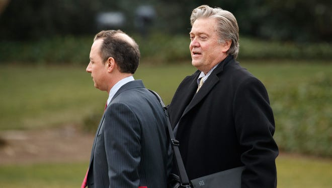 Chief White House Strategist Steve Bannon, right, walks with White House Chief of Staff Reince Priebus to Marine One on the South Lawn of the White House on Feb. 17, 2017.