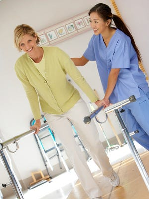 An occupational therapy assistant helps a patient regain mobility.
