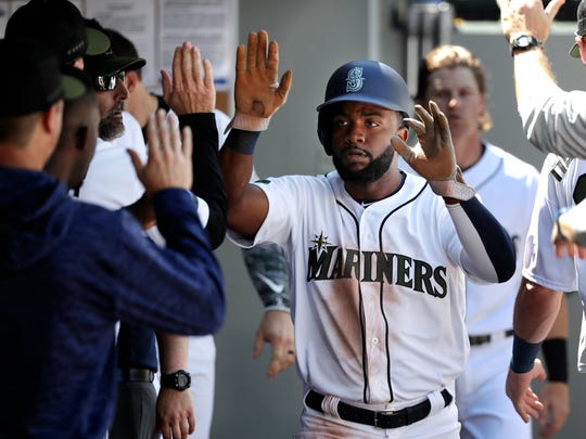 Mariners outfielder Denard Span is congratulated after scoring a run against the Rangers on May 28. Span says he has been impressed with the absence of cliques in the Seattle dugout.