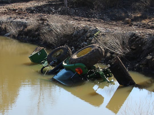 Eldon Cooper's tractor the day after rescuers freed him from the cab. Cooper was trapped upside down and had only a small pocket of water.