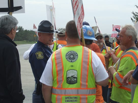 A Michigan State Police trooper talks to picketers