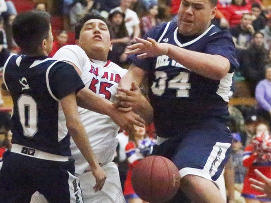 Ruben Mendoza center, of Bel Air fights for a rebound with Del Valle's Jesse Martinez, left, and Jesse Arroyo, right, Friday night at Bel Air. Del Valle prevailed, 47-40.