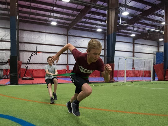 Brandon Boyd (12), left, and Carter Boyd (12) perform a resistance drill during a training session with Sports Specific Training at Slim's Sports Complex in Middletown.