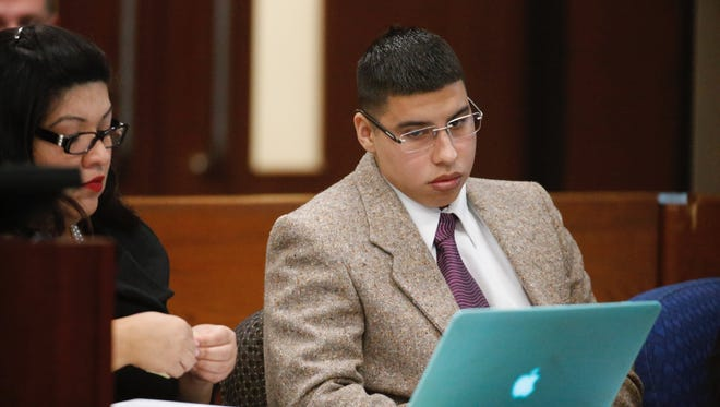 Gustavo Valencia listens to discussions with his lawyer during his trial in a 2014 murder case.