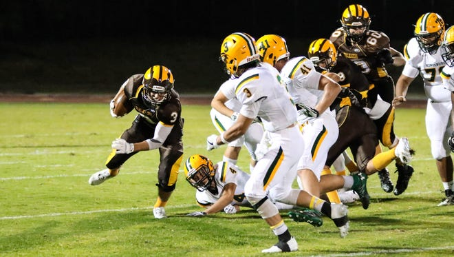 Golden West's Ryan Plaugher (3) breaks a tackle against the Kingsburg Vikings in a non-league football game.