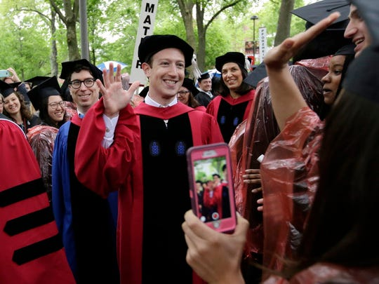 Facebook CEO and Harvard dropout Mark Zuckerberg, center, greets graduating Harvard students as he walks in a procession though Harvard Yard at the start of Harvard University commencement exercises.