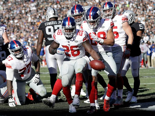 New York Giants running back Orleans Darkwa (26) celebrates with teammates after scoring a touchdown against the Oakland Raiders during the first half of an NFL football game in Oakland, Calif., Sunday, Dec. 3, 2017.