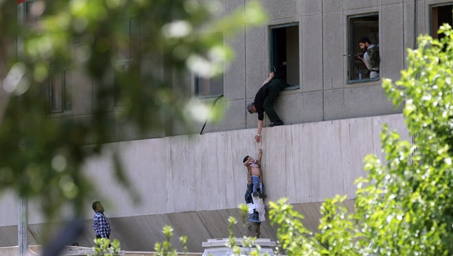 Iranian policemen try to help civilians fleeing from the parliament building during an attack in Tehran, Iran on June 7, 2017.