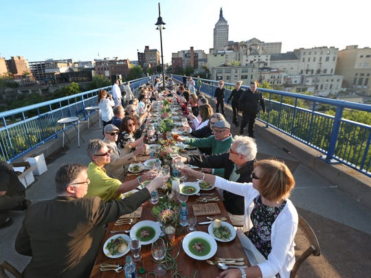 Glasses of wine come together in an opening toast as 200 people attend a special Dinner on the Bridge fundraiser for Greentopia on the Pont de Rennes Bridge in downtown Rochester in 2015.  Clockwise from bottom left are Chris DiFrancesco, Rochester, Kay Aurand, Rochester, Steve and Robin Rauh, Webster.