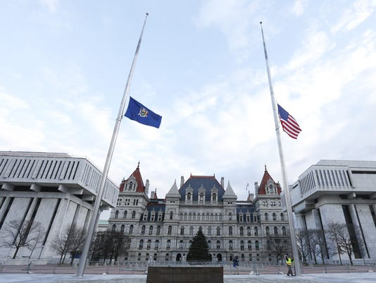 New York State and American flags half-staff in Albany