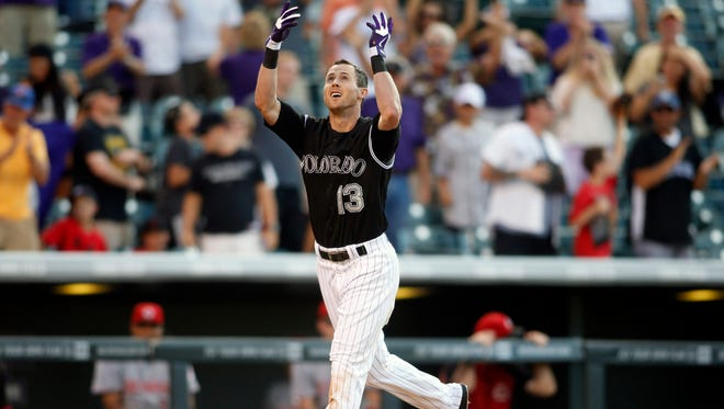 Colorado Rockies center fielder Drew Stubbs (13) throws his helmet into the air as he approaches home plate after hitting a walk off home run during the ninth inning against the Cincinnati Reds at Coors Field. The Rockies won 10-9.