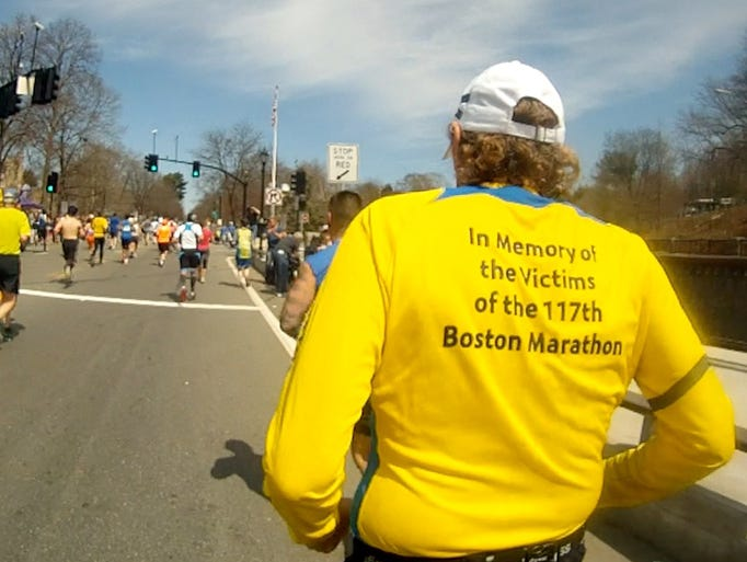 Memorials to the victims of last year's Boston Marathon bombings were seen throughout the course during the running of the 118th Boston Marathon April 21, 2014. Many runners ran with memorials printed on their running clothes.