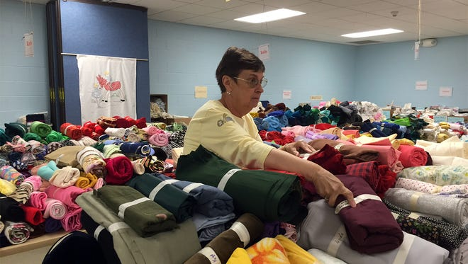 Mary Anne Gallagher, chairwoman of The Salvation Army of York's Women's Auxiliary, sorts through items donated for the upcoming Fabric Fair.