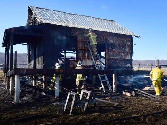 Firefighters continue to work hotspots at a greenhouse that was destroyed by fire Monday afternoon in the 12000 block of Path Valley Road in Metal Township.