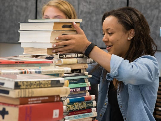 Library aide Alayna Johnson, a Harper Creek High School junior, pulls from the thousands of books in storage to display in the library for Harper Creek's upcoming book sale.