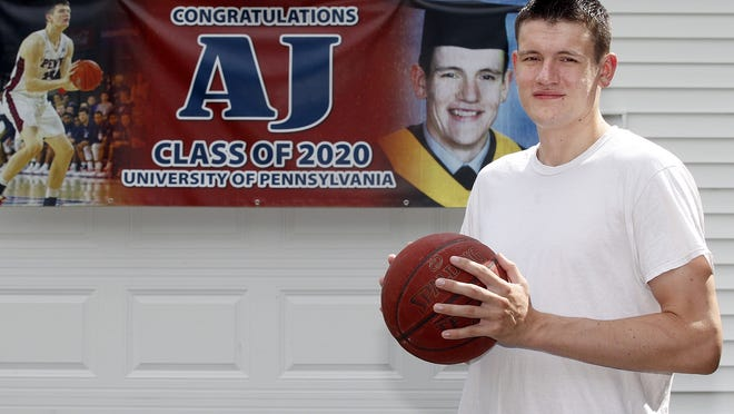 A.J. Brodeur, who just graduated from University of Pennsylvania, poses in front of a banner outside his home in Northborough.