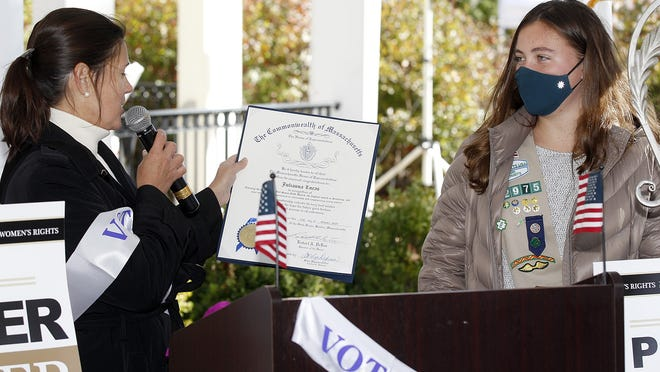 State Rep. Carolyn Dykema, D-Holliston, presents a Gold Award to Julianna Lucas, a Girl Scout from Hopkinton, during Saturday's Women's March at the Town Common. Lucas was recoignized for her young voter registration project at her high school.