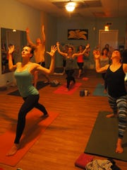 Students hold poses at an evening yoga class at Twisted