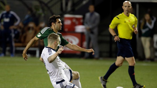 Portland Timbers midfielder Diego Valeri takes a shot as Vancouver Whitecaps defender Jordan Harvey, in white, slides to defend during the second half of an MLS soccer game in Portland, Ore., Saturday, May 2, 2015.  The teams tied 0-0.