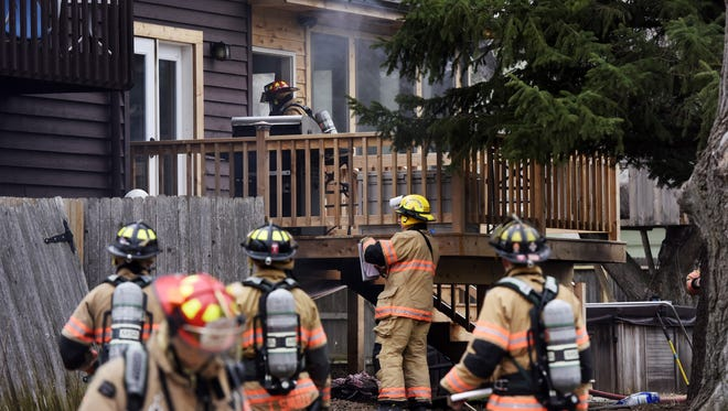 Firefighters clean up at a house fire Wednesday in the 4700 block of South Arthur Circle.