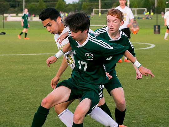 Central Magnet School's Luis Sanchez is jammed between Notre Dame's Milan Card and Justin Hensley. He scored 20 goals this season.