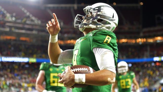 Oregon quarterback Marcus Mariota scores on a 7-yard touchdown run.
