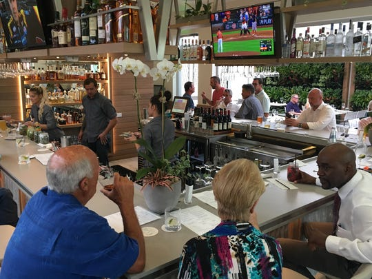 Patrons visit the bar at The Bevy, a new half-indoor,