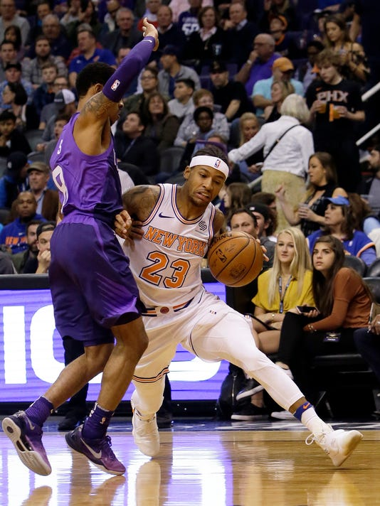New York Knicks guard Trey Burke (23) drives as Phoenix Suns guard Tyler Ulis defends during the first half during an NBA basketball game Friday, Jan. 26, 2018, in Phoenix. (AP Photo/Rick Scuteri)