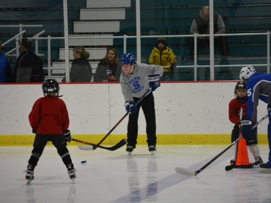 Playing catch during the 'Try Hockey for Free' event are Salem hockey player Joey Driscoll and his buddy for the afternoon, 6-year-old Mark.